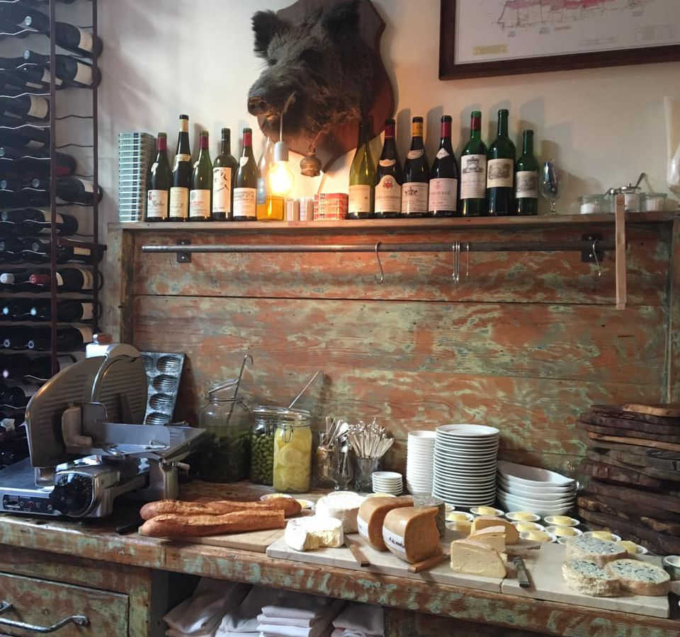 A table spread with charcuterie and cheese beneath a rustic wall featuring wine bottles and candles on a shelf beside a large boar's head for decoration.