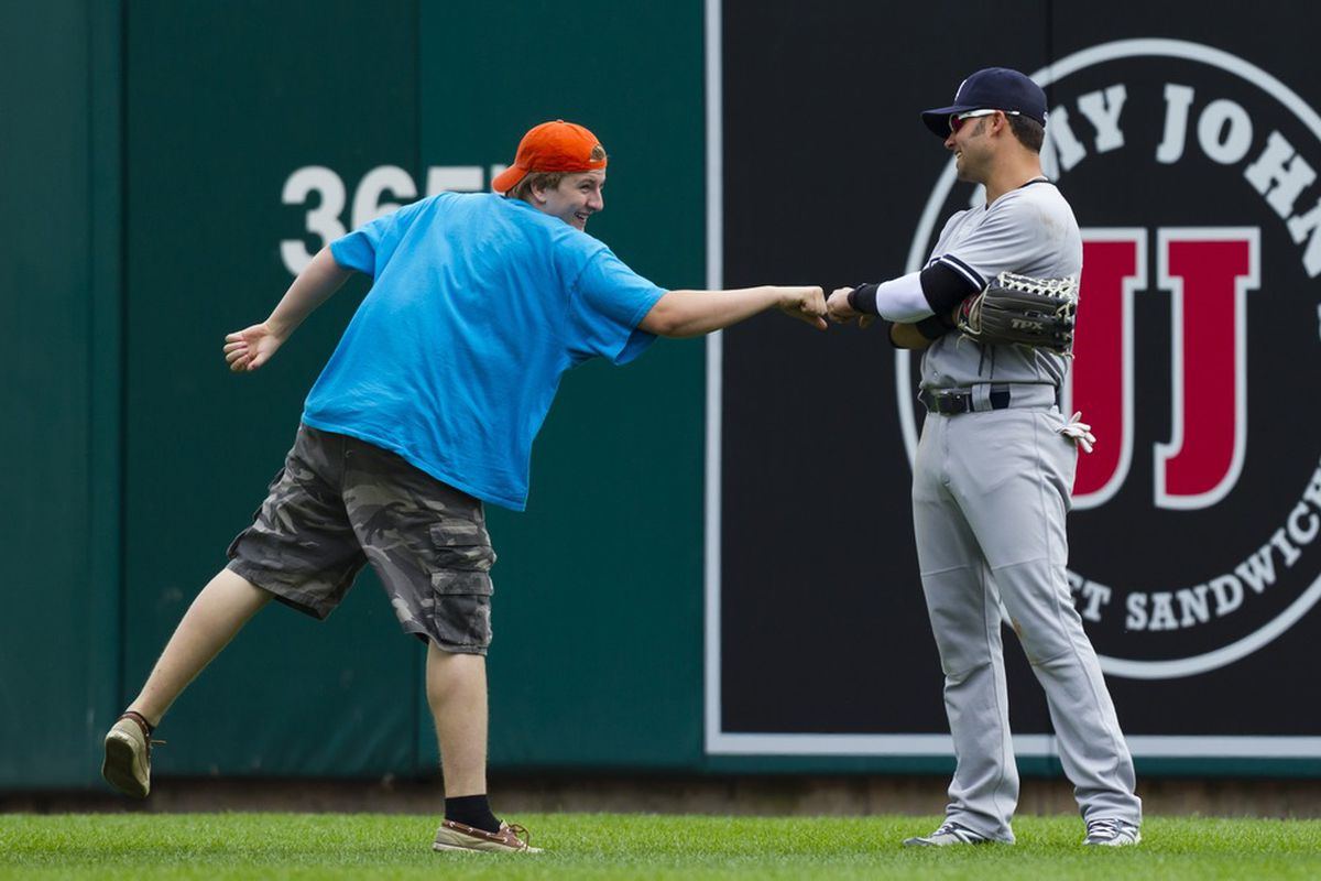 June 3, 2012; Detroit, MI, USA; Fan who entered the field fist bumps with New York Yankees right fielder Nick Swisher (33) during the ninth inning of the game against the Detroit Tigers at Comerica Park. Mandatory Credit: Rick Osentoski-US PRESSWIRE