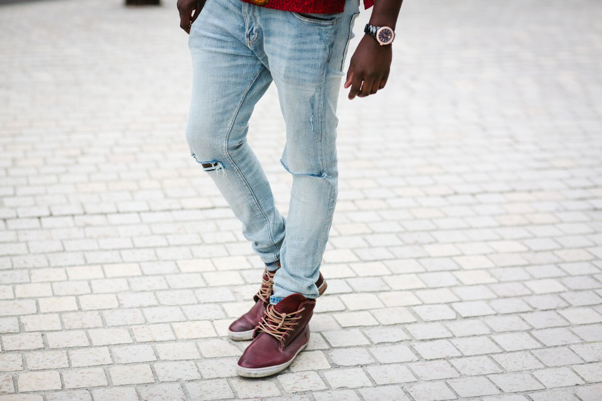 A man in ripped jeans and sneakers on a cobblestone sidewalk.