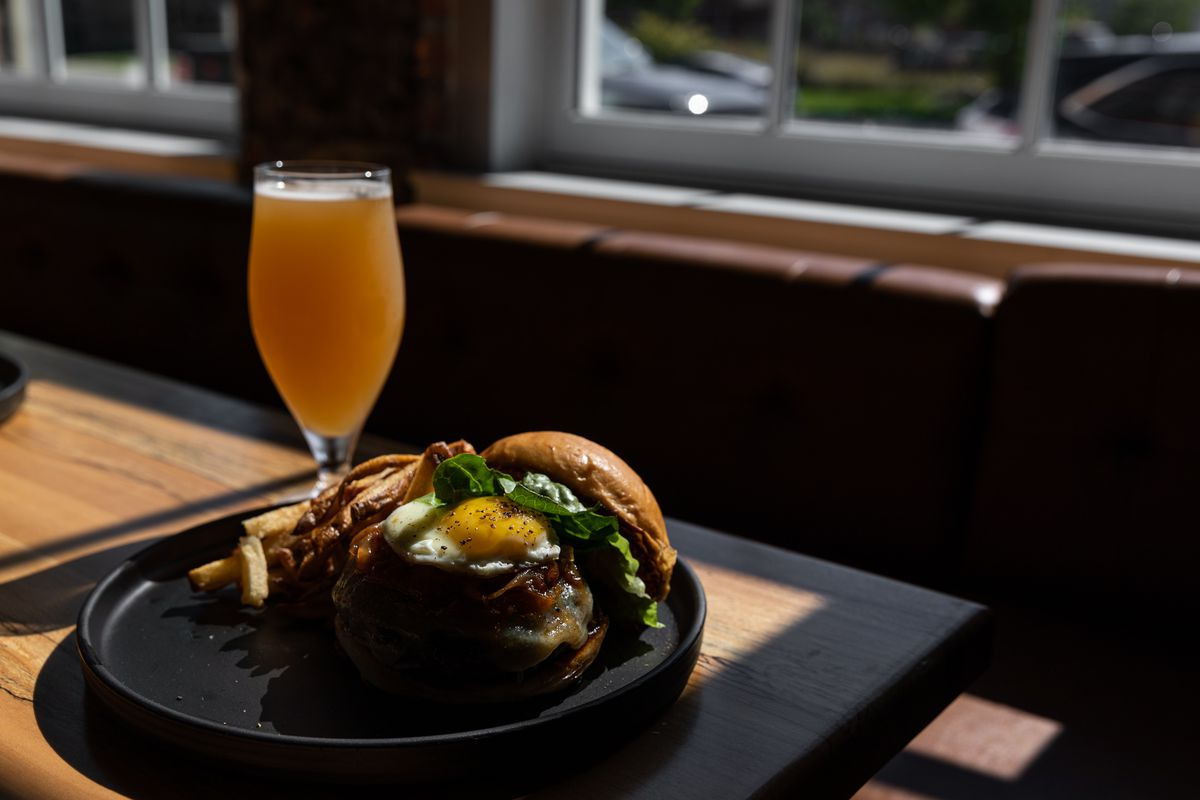A very thick burger with melted cheese, caramelized onions an egg, and lettuce on a black plate with an amber colored beer in a glass behind it.