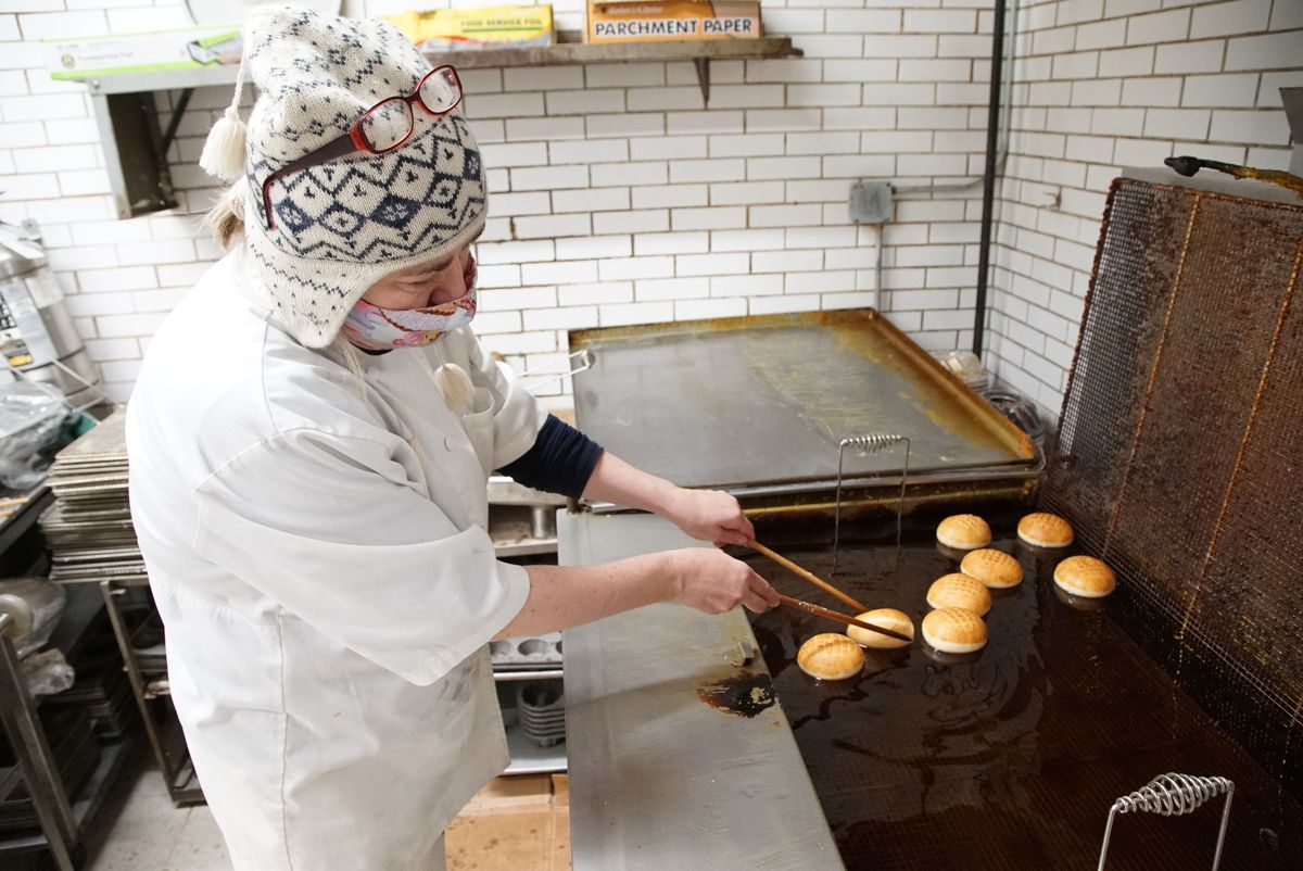 A pastry chef fries paczki in a big container of oil.