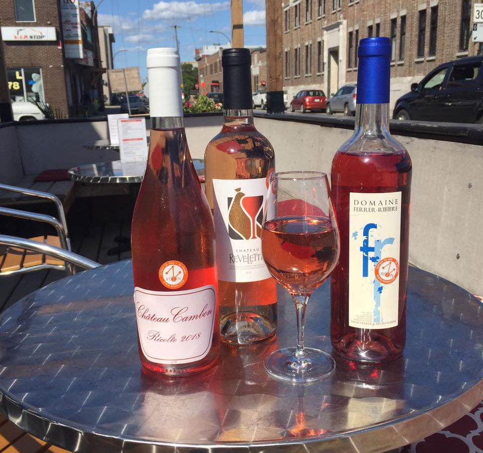 Three bottles and a glass of rosé on a metal table on a terrasse.