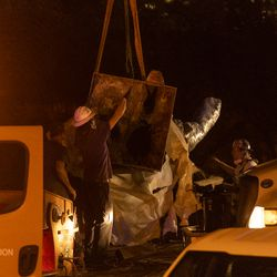A crane moves the Christopher Columbus Statue to a waiting flatbed truck in Grant Park, Friday, July 24, 2020.