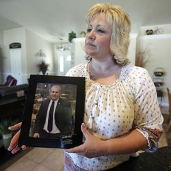 FILE - This July 13, 2016, file photo, Laurie Holt holds a photograph of her son Josh Holt at her home in Riverton, Utah. Venezuelan authorities on Wednesday, July 20, 2016, presented what they said are new details in the case against Josh Holt being held on weapons charges. Holt traveled to Venezuela last month on a tourist visa to marry a fellow Mormon he met on the internet. At the time of the arrest June 30, Holt's new wife, Thamara Caleno, was waiting for a U.S. visa so the pair could travel to his home in a suburb of Salt Lake City.