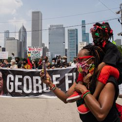 Faith leaders and community activists raise their fists during a march that commemorates Juneteenth in downtown Chicago on June 19, 2020.