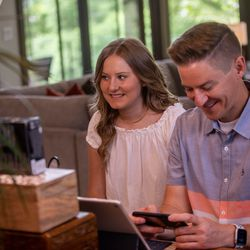 """Savanna Shaw and Mat Shaw listen to a recording of their cover of the song """"Shallow"""" in their family's home on Thursday, May 14, 2020. The father-daughter duets went viral on YouTube as they shared their passion for music amid the COVID-19 pandemic. """"The one thing more contagious than a virus is hope and so we're just doing our small part in the world to spread some hope,"""" Mat Shaw said."""