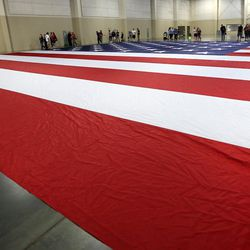 People look at a giant American Flag at the South Towne Expo Center in Sandy on Wednesday, May 31, 2017. The flag, which measures 78 feet by 125 feet, will fly between the two peaks at Grove Canyon in Pleasant Grove on the morning of July 4th. The organization Follow the Flag believes it will be the largest American flag ever flown.