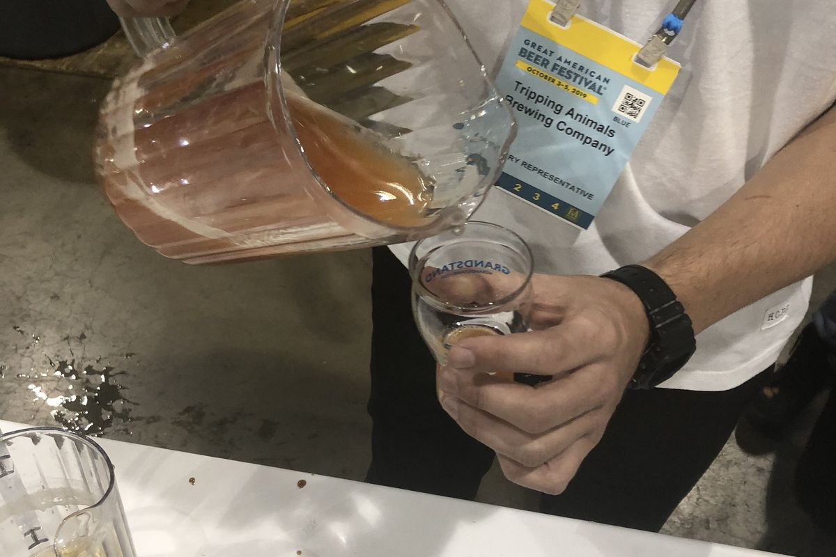 A photo of a brewer pouring Tripping Animals Brewing's Moskittle beer into a glass at the Great American Beer Festival