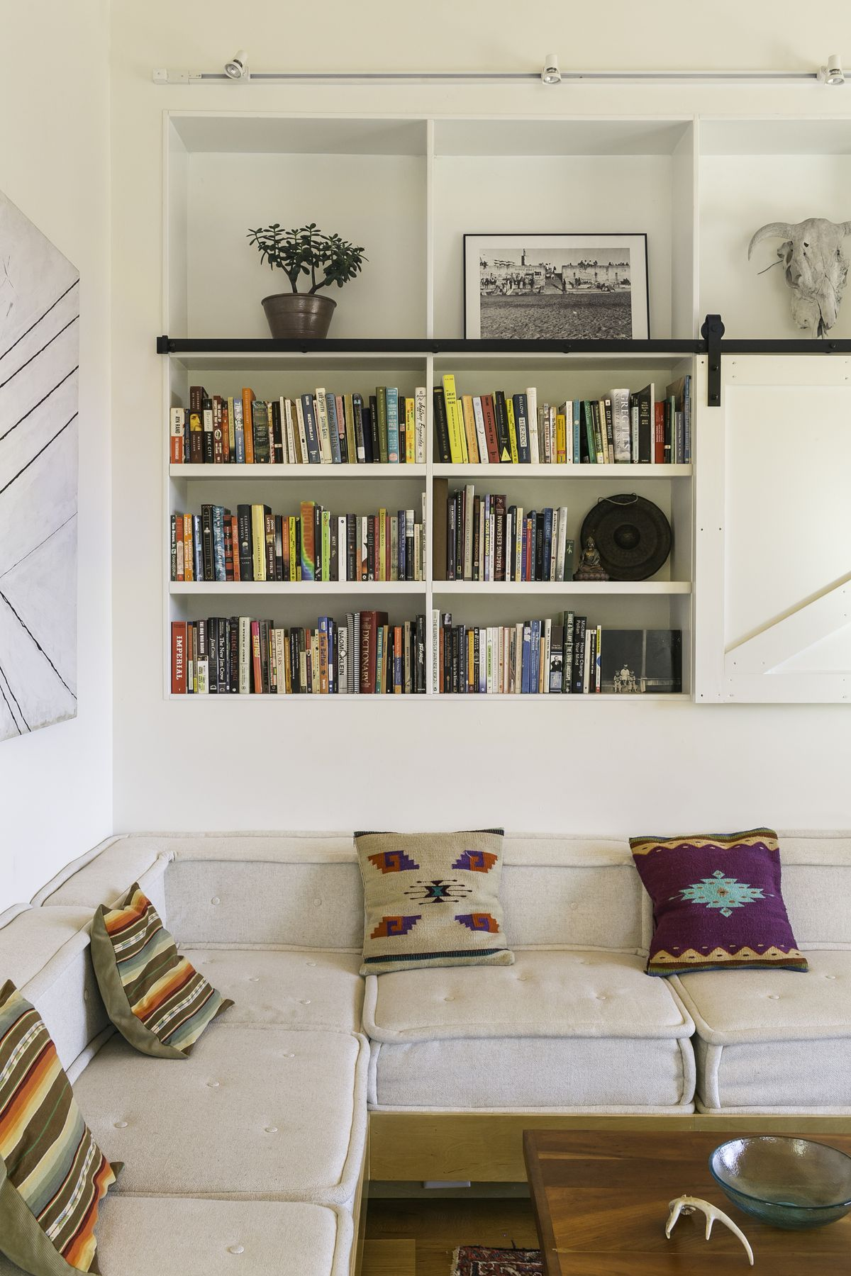 Built in bookshelf with lots of books, and a custom sofa with grey cushions and patterned pillows.