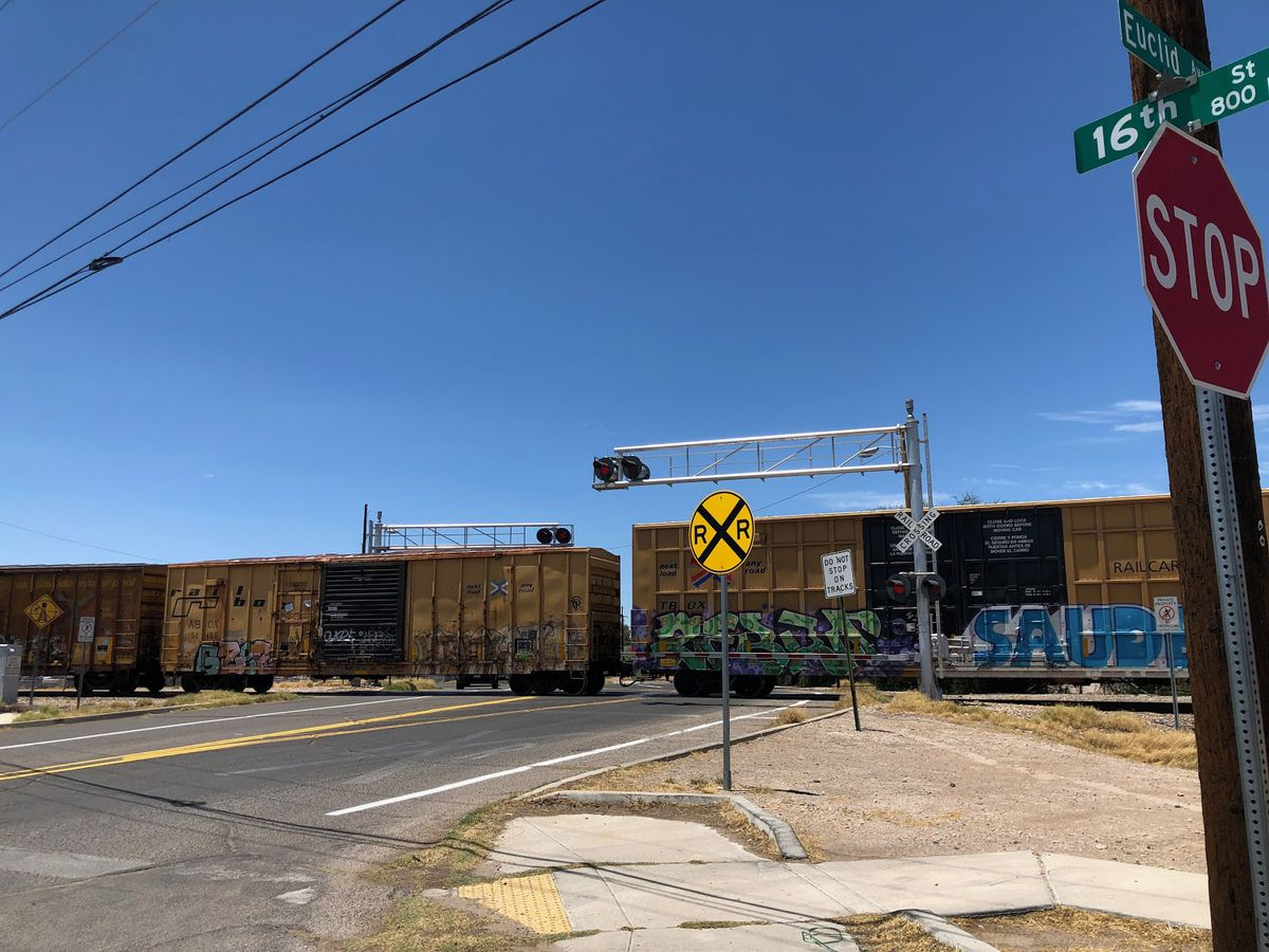 A freight train crosses through an intersection with a railroad crossing sign at the center.