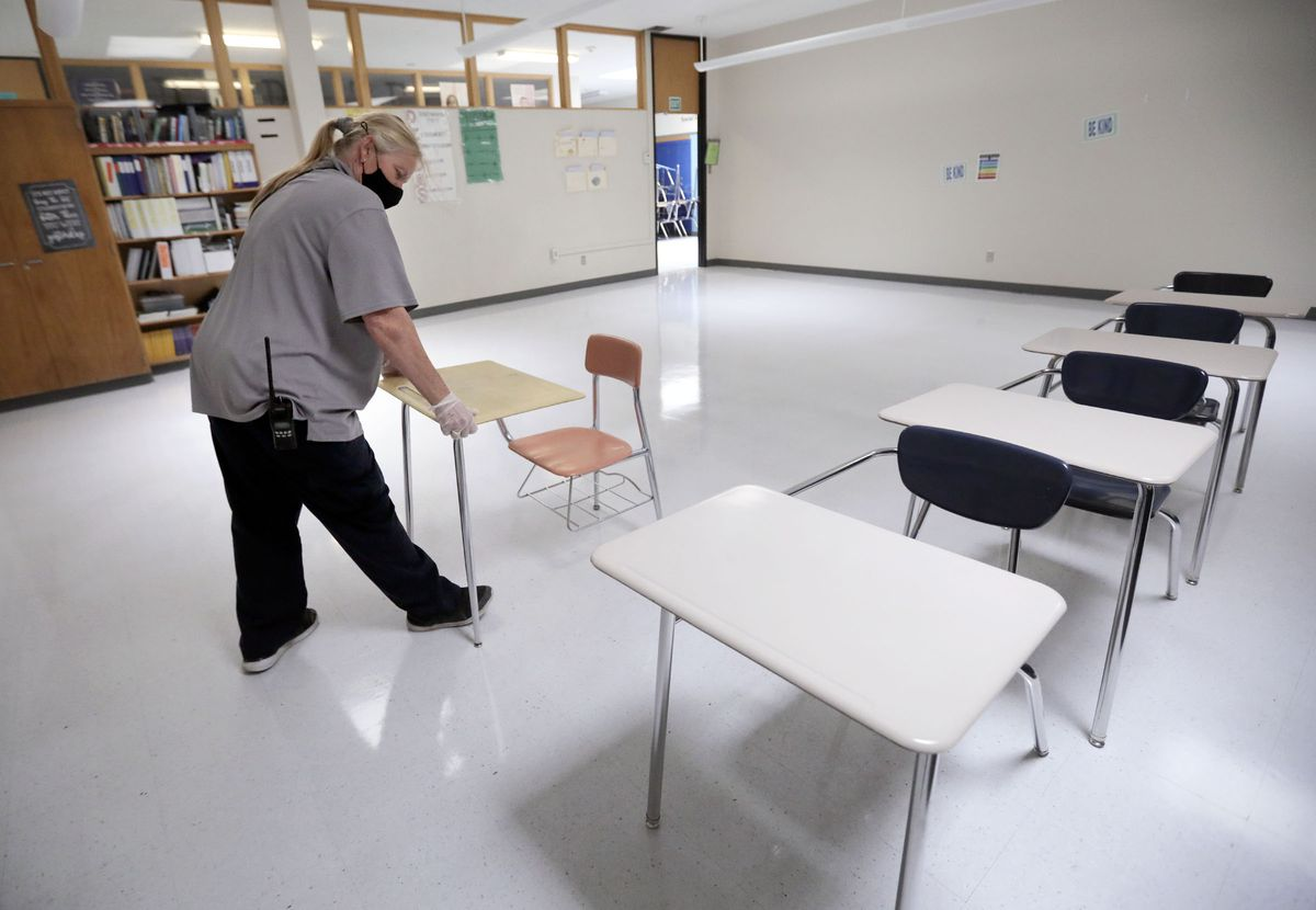 Stephanie Harrill, Skyline High School custodian, sets up desks in a cleaned classroom to get ready for the start of school at Skyline High School in Millcreek on Thursday, July 23, 2020.