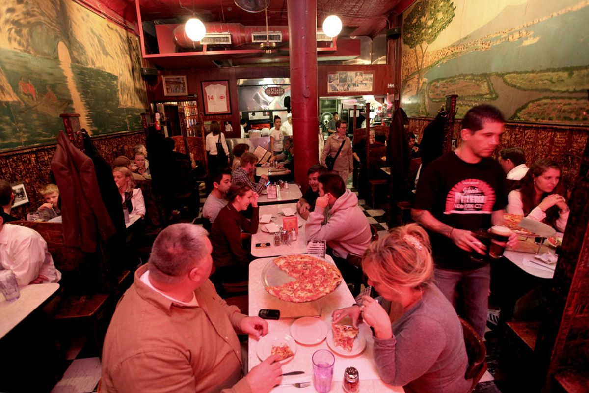 A busy dining room full of people eating pizza