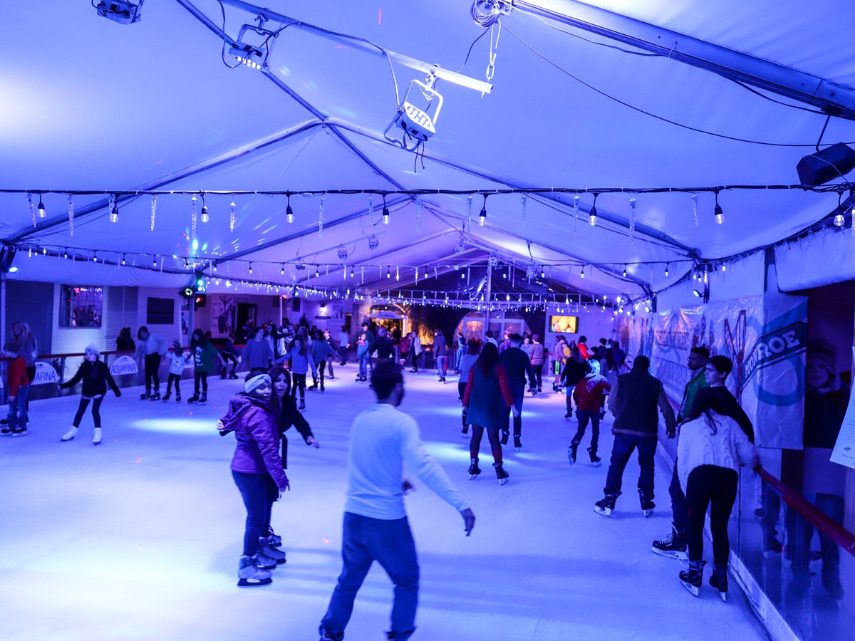 The interior of The Rink at Park Tavern in Atlanta. People are skating on the ice rink. The room is illuminated in purple light.