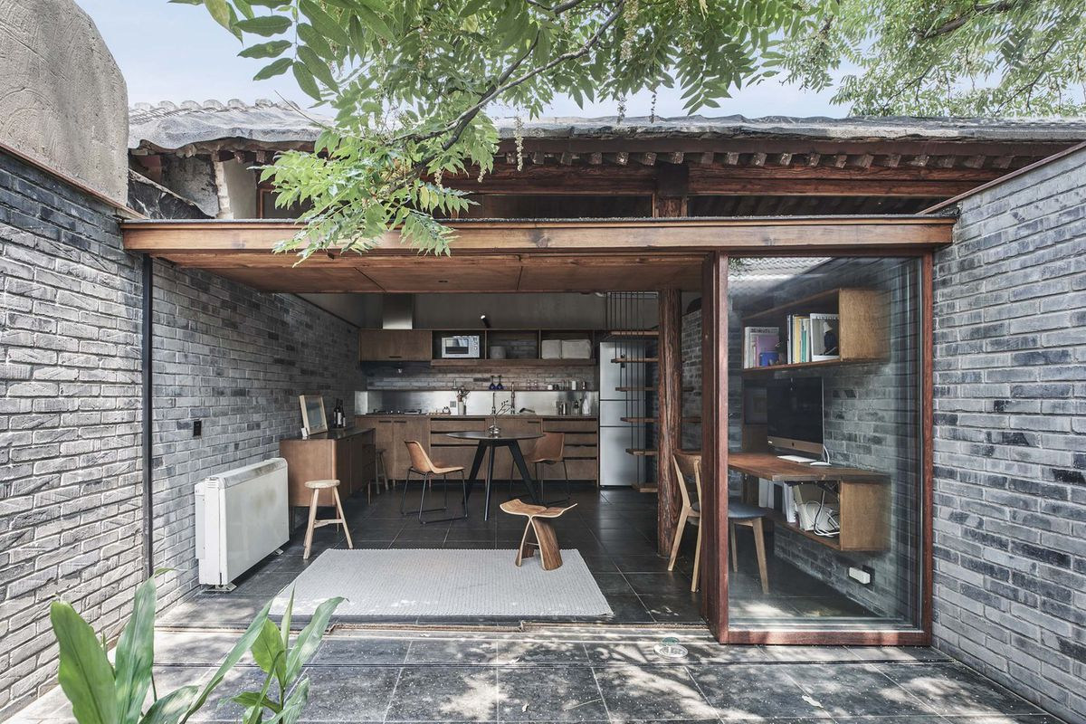 Small brick home with doors open to a private courtyard.