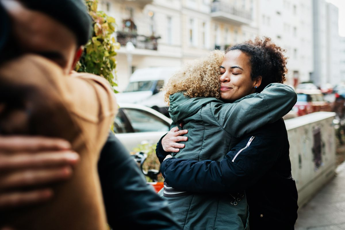Two friends embrace in the street.