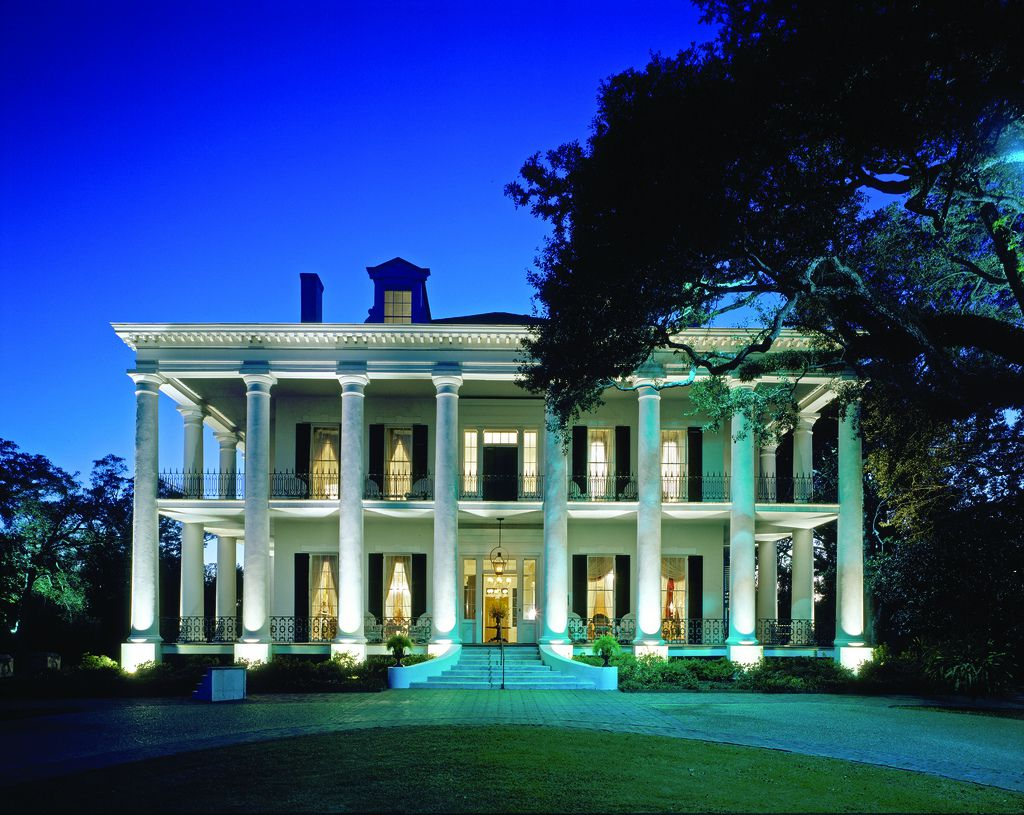 A large white house with columns on the front facade. There are trees and a lawn in front of the house.