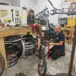 A man works on a children's bike at the Ogden Bicycle Collective, while a child watches him.