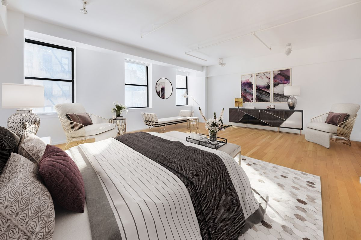 A bedroom with a medium-sized bed, hardwood floors, three windows, a rug, and white walls.
