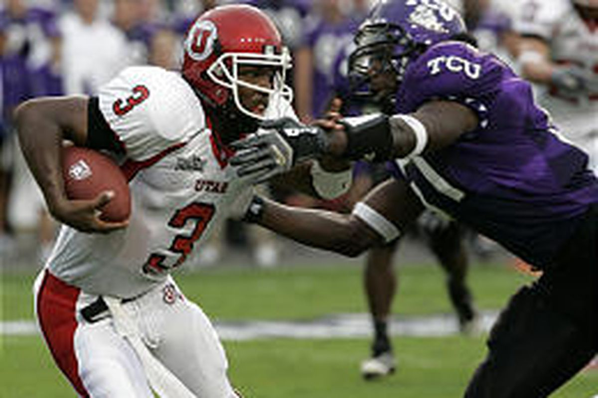 Utah quarterback Brian Johnson, left, scrambles past Texas Christian linebacker Robert Henson for a gain in the first quarter of Thursday's game in Fort Worth, Texas. The Utes lost, ending an 18-game win streak.