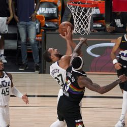 Utah Jazz's Donovan Mitchell (45) looks on as Rudy Gobert (27) goes up for a contested shot by Denver Nuggets' Torrey Craig (3) during the second half an NBA first round playoff basketball game, Tuesday, Sept. 1, 2020, in Lake Buena Vista, Fla. The Nuggets' Jamal Murray (27) looks on during the play.