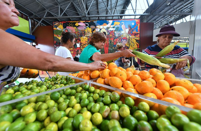 Customers choose tangerines, limes, corn, and other produce.