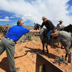 Interior Secretary Ryan Zinke shakes hands over a barbed wire fence with Willie Greyeyes after hiking to an overlook in the Butler Wash area of the Bears Ears National Monument to view ancient ruins on Monday, May 8, 2017.