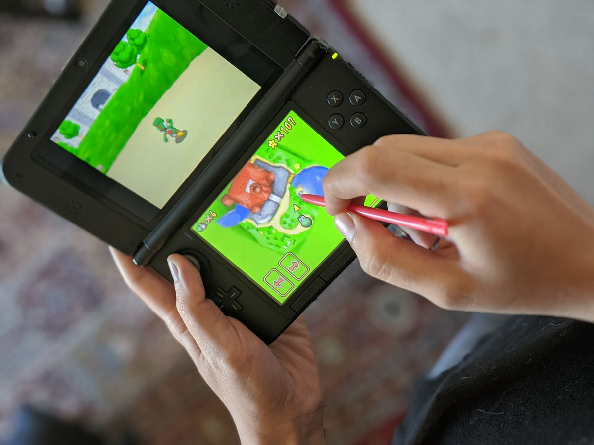 a person using a stylus to play Super Mario 64 DS on a Nintendo 3DS