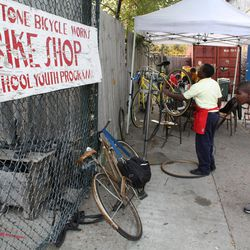 In this Tuesday, Oct. 11, 2010 photo, bike apprentices inspect customers' bikes outside the Blackstone Bicycle Works bike shop in Chicago. The bike shop has an after-school program that gives students the chance to work 25 hours in the shop to earn a bike.