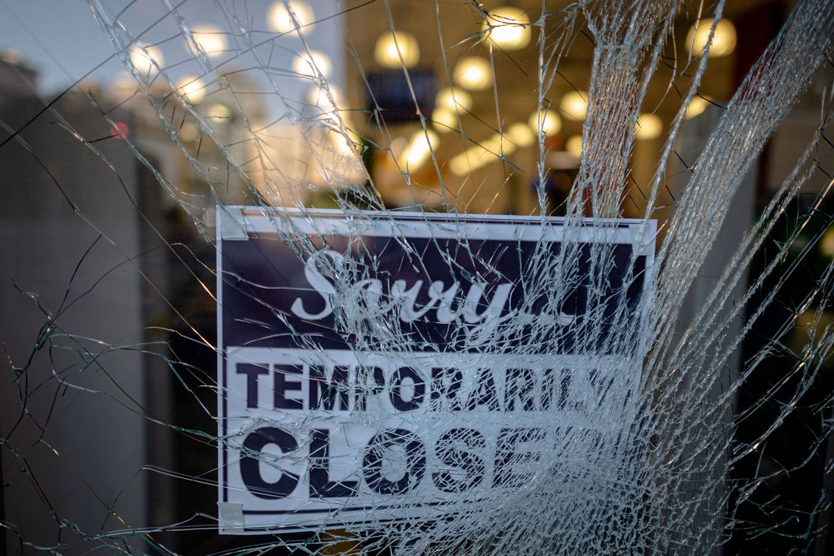 """A sign reading """"sorry temporarily closed"""" behind cracked glass in Manhattan"""