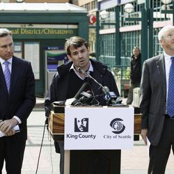King County Executive Dow Constantine, left, looks on as Chris Hansen, center, the venture capitalist who wants to build a new sports arena in Seattle, talks to reporters as Seattle Mayor Mike McGinn, right, looks on, Thursday, April 5, 2012, in Seattle. Hansen said he will pay for a study to determine the impacts on traffic and parking around his proposed stadium site south of Seattle and near Safeco Field and CenturyLink Field where the MLB Seattle Mariners and the NFL Seattle Seahawks play.