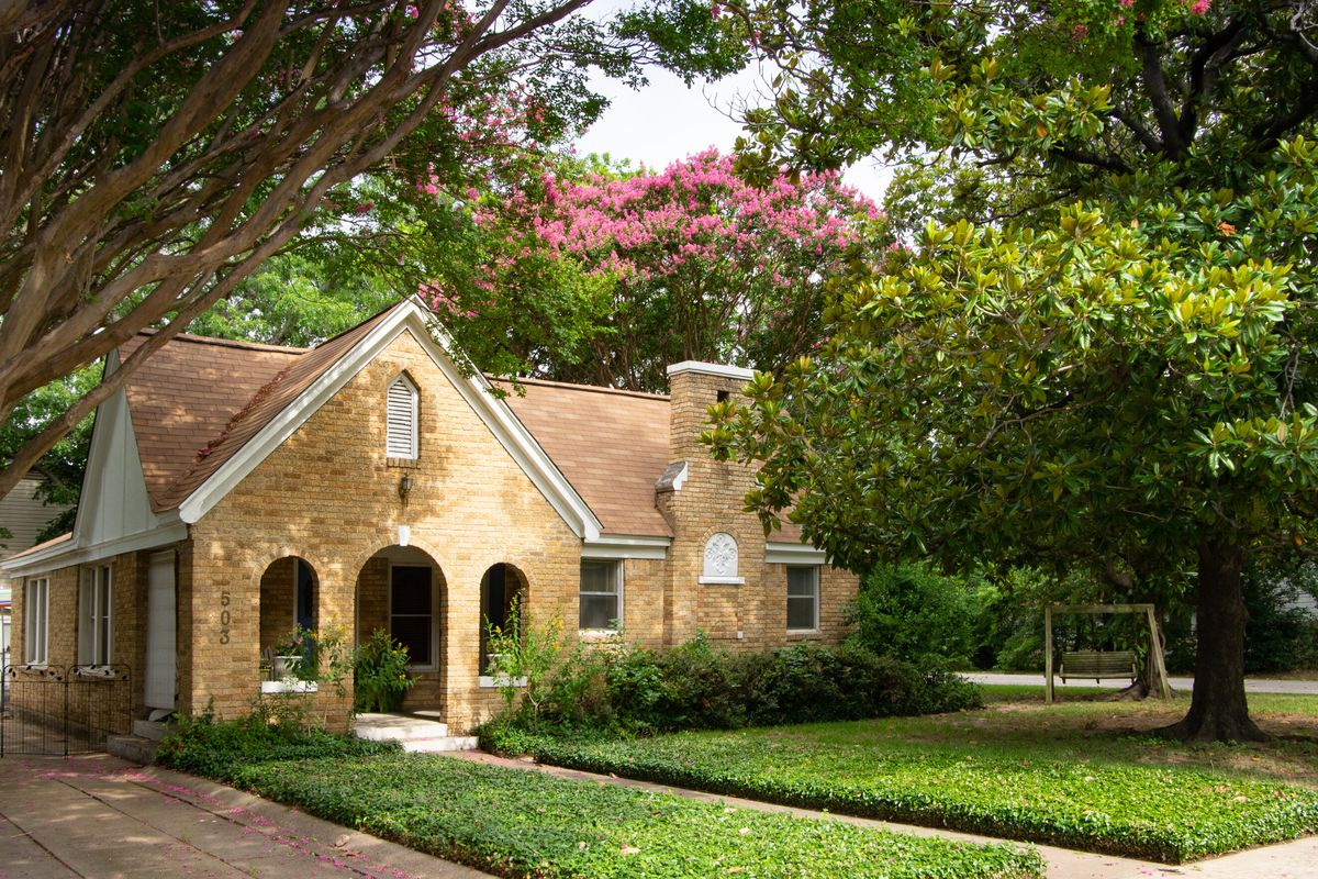 Stone house surrounded by large, blooming trees with green yard.