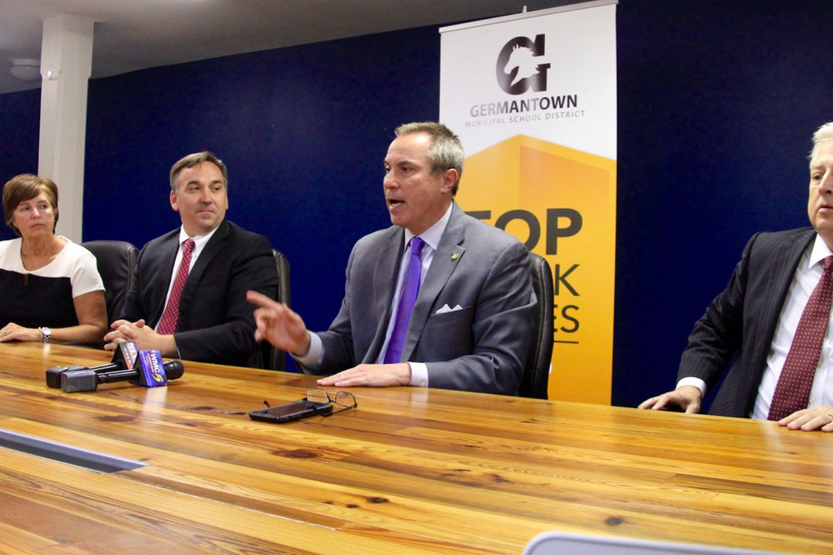 Germantown Mayor Mike Palazzolo (center) answers questions from reporters about a $25 million offer to buy three schools from Shelby County Schools.