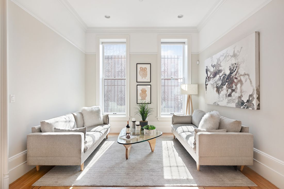 A living area with two windows with decorative railings, two grey couches, and a glass coffee table.