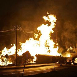 FILE - In this June 19, 2009 file photo, a car at right is seen engulfed in flames from rail cars loaded with ethanol that derailed in Rockford, Ill. A Rockford woman died as she tried to flee the derailment.  For two decades, one of the nation's most common types of rail tanker, known as a DOT-111, has been allowed to haul hazardous liquids from coast to coast even though transportation officials were aware of a dangerous design flaw that almost guarantees the car will tear open in an accident. The rail and chemical industries have committed to a safer design for new tankers, but they do not want to modify tens of thousands of existing cars. That's despite a spike in the number of accidents.