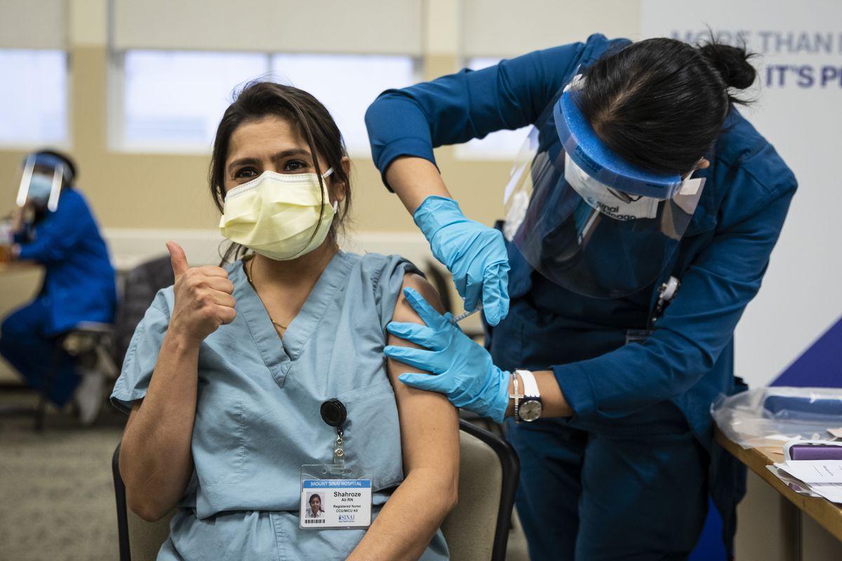 Nurse Evelyn Aranda administers the Pfizer-BioNTech COVID-19 vaccine to nurse Shahroze Ali in December.