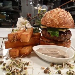 Sho Shaun Hergatt Burger: 5 oz shortrib burger with lamb bacon, truffle mayonnaise, carmelized onion and pickled ramp compote, tomato, and ramp leaves on a housemade brioche bun. It's offered for lunch and dinner in the Pearl Room and Black bar for $20 or