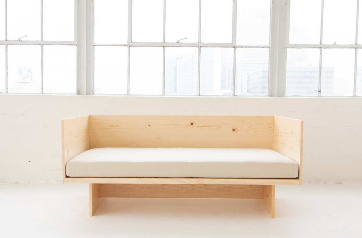 Pale wood day bed in a well-lit space.
