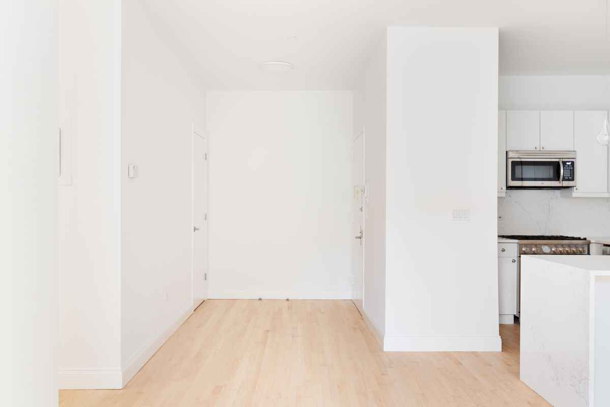 A foyer with hardwood floors and white walls.