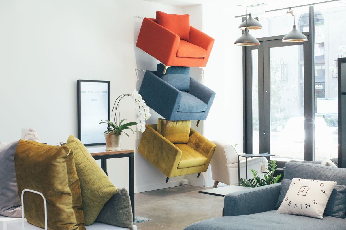 White-walled shop with colorful armchairs suspended on wall and other furniture in front