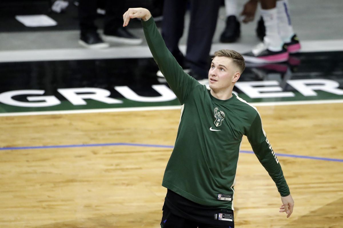 Milwaukee Bucks guard Sam Merrill holds his arm in the air after taking a warmup shot.