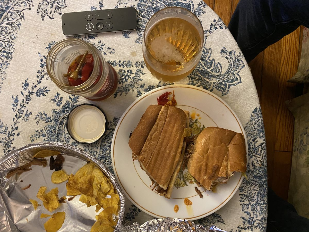 A pressed Cuban sandwich from Guantanamera sits on a patterned tablecloth next to a beer and a takeout tin with scattered plantain chips