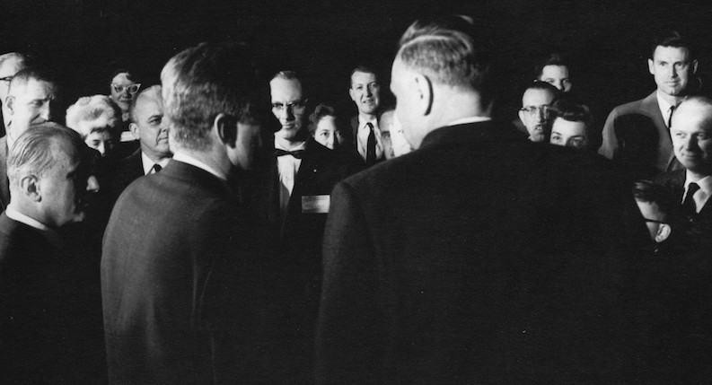 Ted Petry (center, in bow tie and glasses), is visible facing President John F. Kennedy at a gathering to commemorate the 20th anniversary of the first controlled nuclear reaction.   John F. Kennedy Presidential Library and Museum