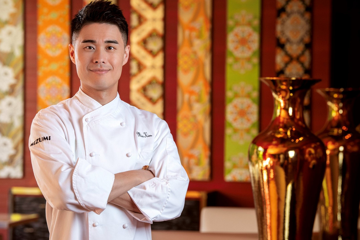A chef stands with his arms crossed