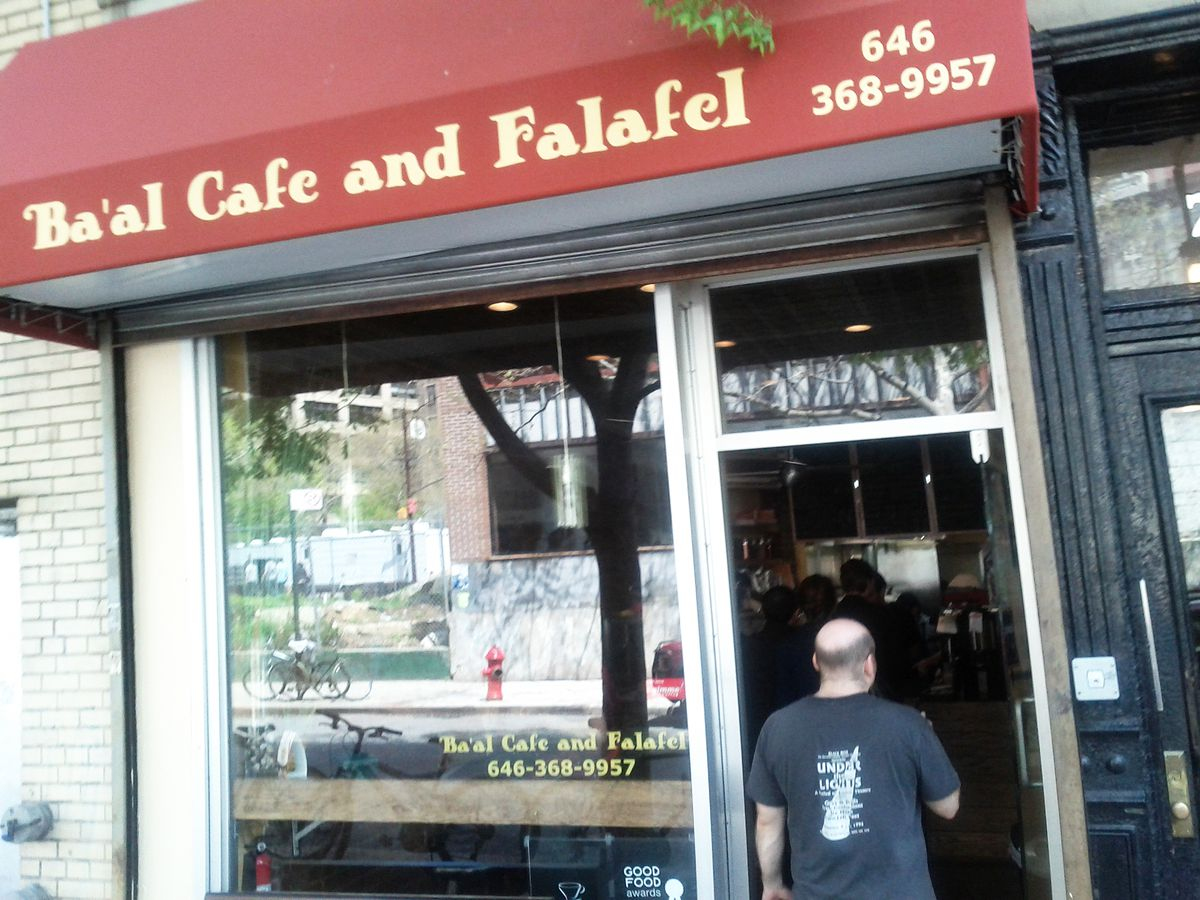 A narrow storefront with a dark red awning advertising falafel and a partially bald person going in.