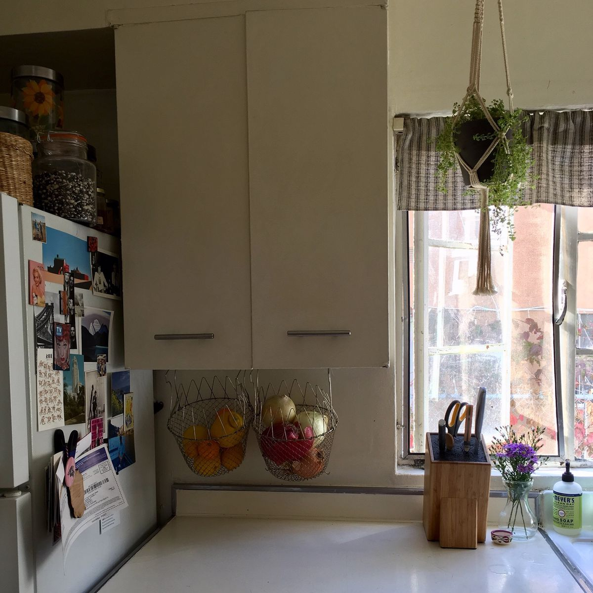 Kitchen with two metal baskets hanging from the underside of cabinets.