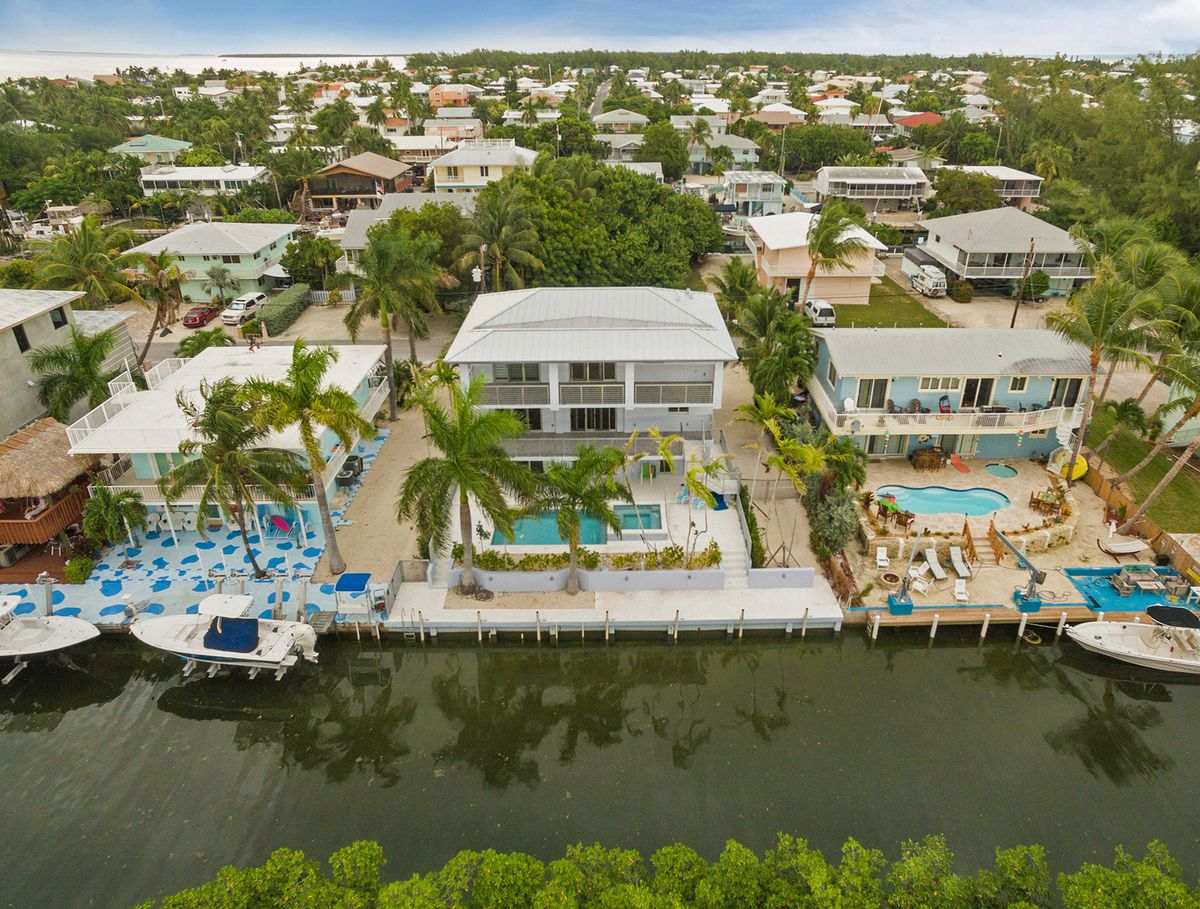 Aerial view of a modern build in the FLorida Keys sitting on a canal with a light gray roof, backyard pool, and palm trees