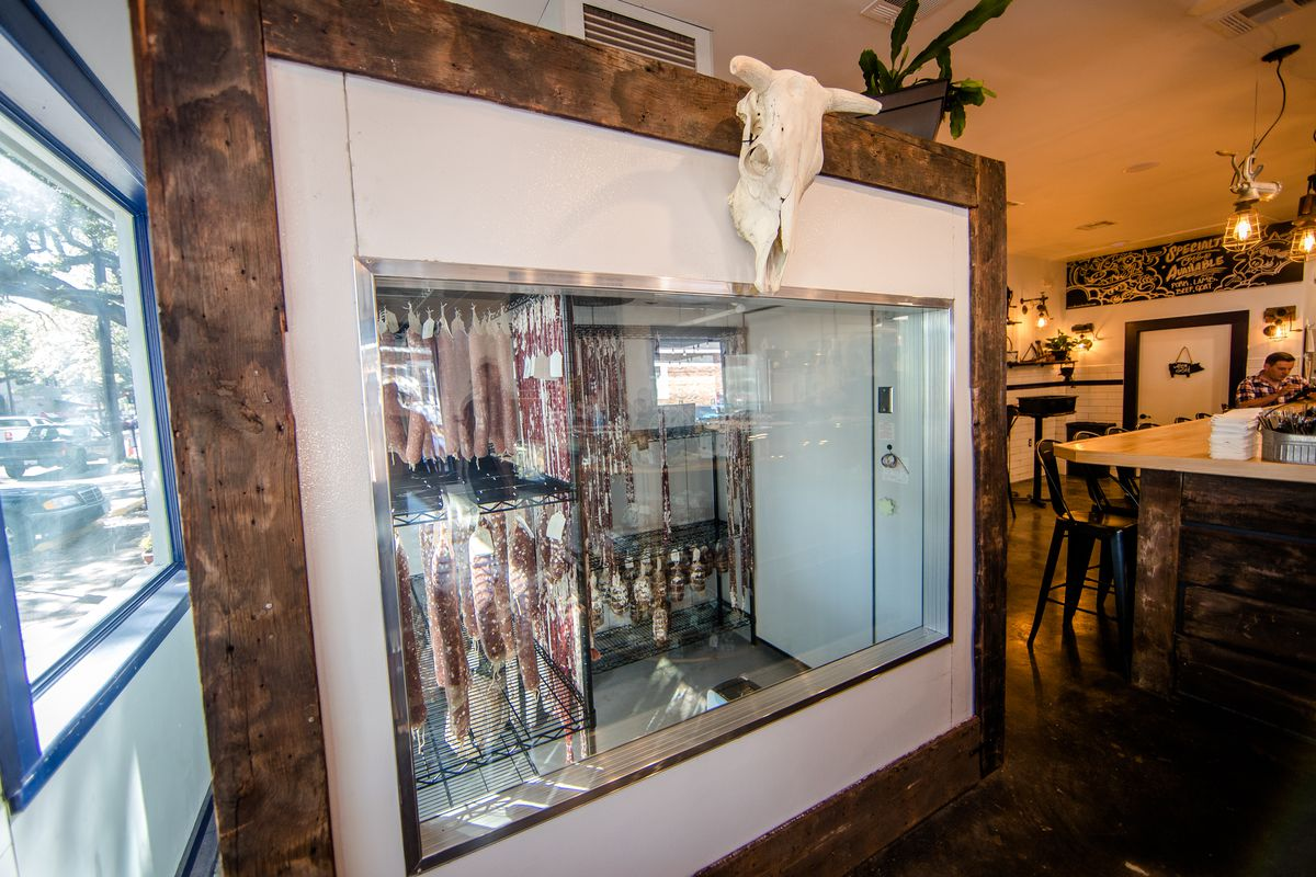 A salami room inside piece of meat; glass walls expose hanging cuts of curing meat