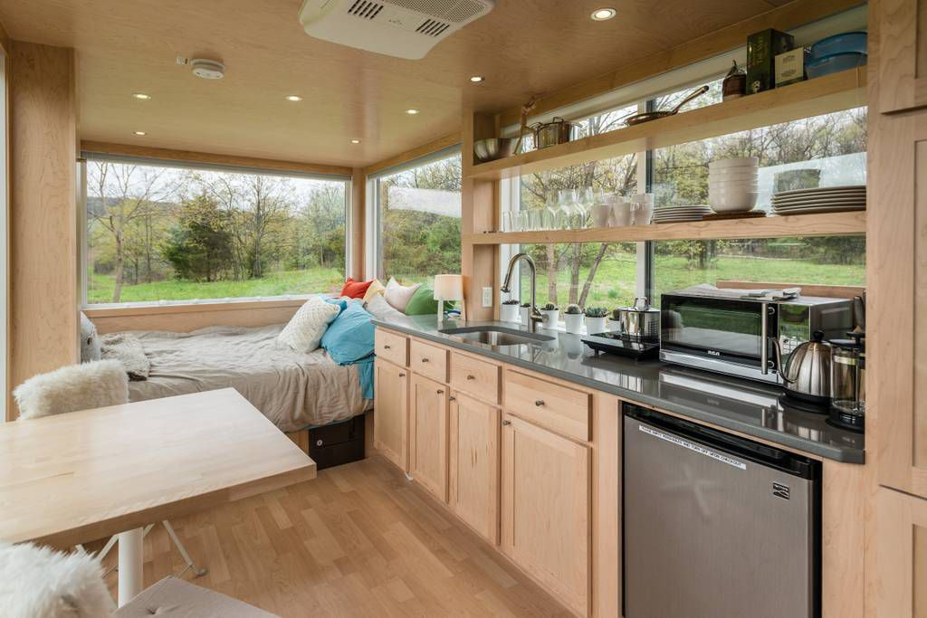 The inside of a tiny home that is covered in light wood, with a bed at one end next to large windows, and a small kitchen with a dishwasher, toaster oven, and open storage with dishes.