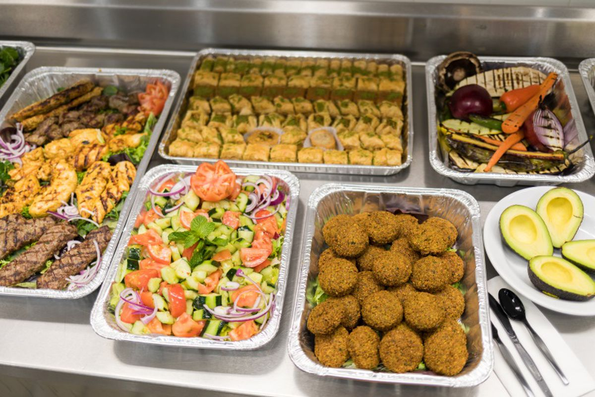 A spread of Mediterranean food from Falafel King in Downtown Boston, which includes salad, falafel, and grilled vegetables.