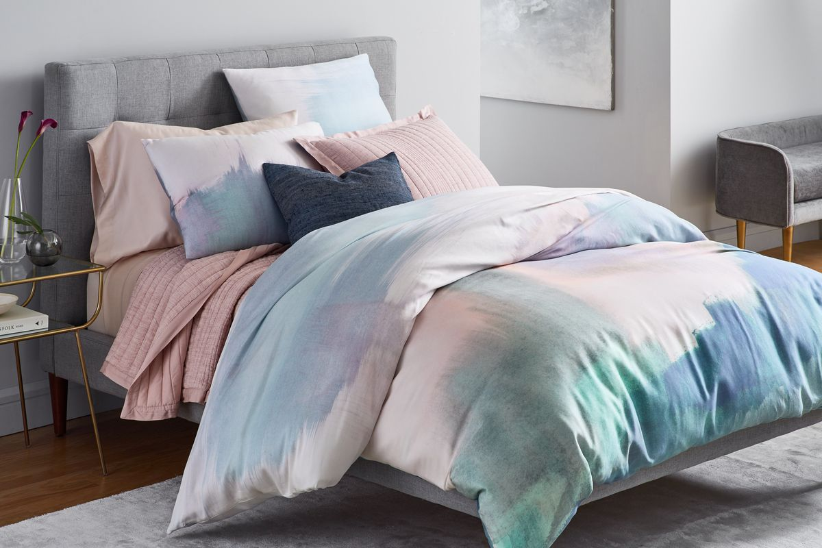 A bed made with West Elm linens and pillows.